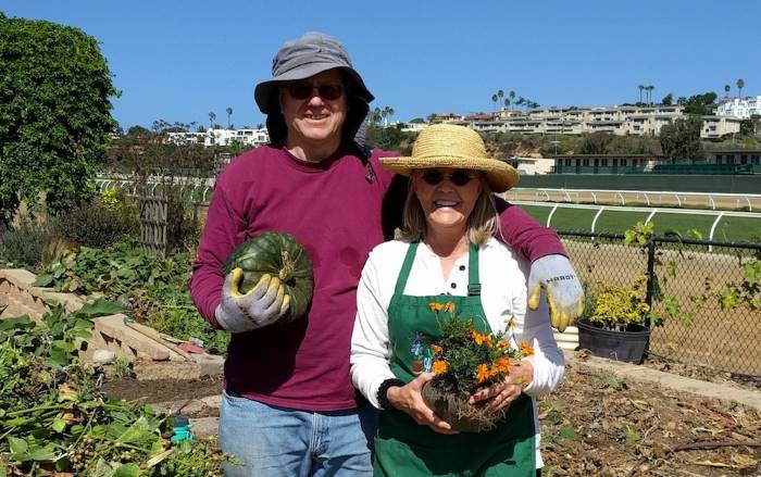 two smiling docents holding produce and flowers in a field